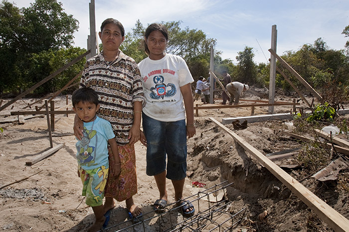 tsunami survivor and widow, standing with her children,